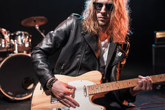 Rock star in eyeglasses playing hard rock music with bass guitar on stage. Handsome rock star in eyeglasses playing hard rock music with bass guitar on stage Stock Images