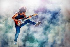 Rock star guitarist jumping and playing electric guitar Stock Photography