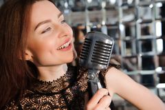 Rock star. Girl singing in retro microphone stock images