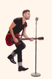 Rock star singing with guitar. And microphone Stock Photo