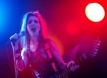 Rock star singing on stage. Young rock star singing with stage lights on background Stock Photography
