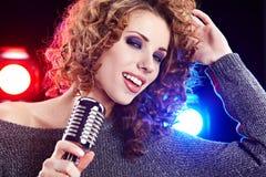 Rock star. Woman  singing in retro mic Royalty Free Stock Photo