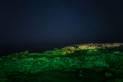 Rock. starry night sky. sea. Sea highlighted green laser pointer. Stock Photography