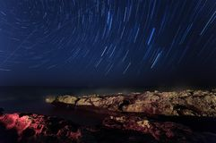 Rock. starry night sky. sea. Sea highlighted . star trails royalty free stock photography