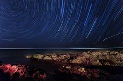 Rock. starry night sky. sea. star trails. polaris star royalty free stock photo