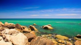 Rock Stony Beach Azure Sea Skyline. Camera moves from round rock to stony beach along azure sea up to skyline waves splash stock footage