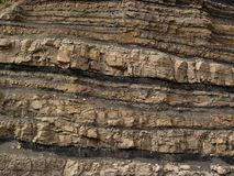 Rock strata. Road grade cutaway showing the different rock layers - strata Stock Image