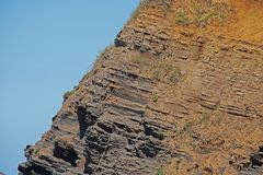 ROCK WITH STRATUM LAYERS AT THE COAST. Molded rock layers on a sandy bluff at the coast Stock Photography