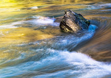 Rock in stream - long exposure sundown. Standing firm, against t Royalty Free Stock Photo