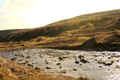 Rock strewn stream in baron moorland. A meandering stream with various sized rocks through baron moorland showing a rugged hillside and differing shades of royalty free stock images