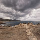Rock striations near Ile Rousse in Corsica and stormy clouds. A line of rock striations on the coast of Corsica with Ile Rousse in the distance under dark storm Royalty Free Stock Images