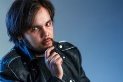Rock style or biker theme. A portrait of a black-haired guy with a beard in a black leather jacket holds a hand on his chin. Blue royalty free stock photos