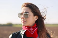 Rock style. Close up shot of dark haired thoughtful woman dressed in leather jacket, red bandana and sunglasses, focused into dist stock images