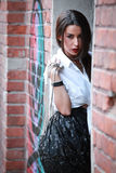 Rock styled girl posing in front of brick wall Stock Photo