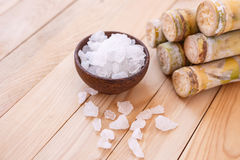 Rock sugar and sugar cane on wooden table background Stock Image