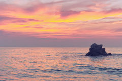 Rock at sunset on sea with pink colors Stock Images