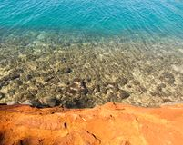 Rock and Surf Contrast. Red lava rock contrasted with blue water and reef Stock Photo