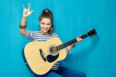 Rock on with teenager girl and guitar music. Blue wall background Stock Photos