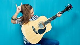 Rock on with teenager girl and guitar music. Blue wall background Royalty Free Stock Photos