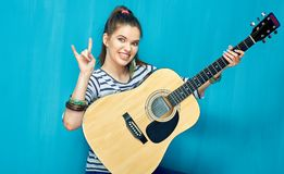 Rock on with teenager girl and guitar music. Blue wall background Royalty Free Stock Photography