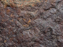 Rock texture: close-up of a red-brown stone useful as background Royalty Free Stock Images