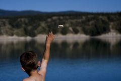 Rock throwing boy. Boy throwing rock into a  mountain like lake Royalty Free Stock Photography