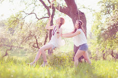 Rock Two girls. Two young women wear long dresses Wesse in evening light on a meadow. One sits on the swing un the other pushes her to laugh Stock Photos