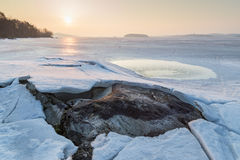 Rock under cracked ice at a frozen lake Royalty Free Stock Images