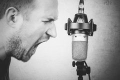 Rock vocalist. Screaming to the studio microphone on textured background Stock Image