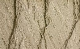 Rock Wall with 3 Cracks. Close up of a tan rock on a building exterior with 3 cracks Royalty Free Stock Photography