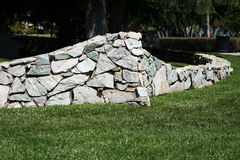 Rock wall background. Retaining wall built of natural rock stock photography