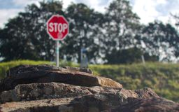 A rock wall leading to a blurred background containing a stop sign stock images
