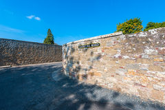 Rock wall by a road. In downtown Jedburgh, Scotland stock photos