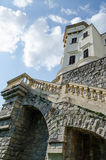 Rock wall and stairs at beautiful restored white castle with red tiles and blue sky in Czech Republic Royalty Free Stock Photos
