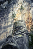 Rock wall. Stone peak standing against high rock wall Stock Photo