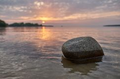 Rock in the water. With the sunset in the background royalty free stock photography