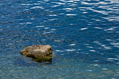 Rock in the water. Rock in calm blue rippling water on the coast of the Adriatic sea royalty free stock photo