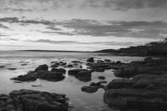 Rock and Water Landscape. A sunrise, but in greyscale Royalty Free Stock Photos