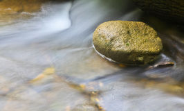 A rock with water motion. A small rock in the river with water motion at Areuse Gorge, Neuchatel, Switzerland Stock Photos