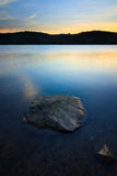 A rock in the water with sunset Stock Image
