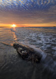 Rock and waves with dramatic sunset clouds Royalty Free Stock Photography
