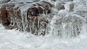 Well soaked. A rock well wet by incoming tide at a beach south of Durban SA Royalty Free Stock Photos