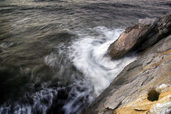 The rock and the whirlpool. Marine wave moved by effect of the long exposure breaking against a rock and creating a whirlpool together with it Stock Photos