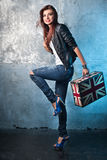 Rock young woman with suitcase with British flag. Portrait of casual young woman with suitcase with British flag, metal wall as a background Royalty Free Stock Photography