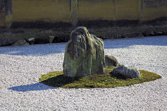 Rock in Zen Garden. Moss covered rocks in zen garden surrounded by raked gravel royalty free stock photos