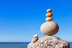 Rock zen pyramid of colorful pebbles on a beach on the background of the sea. Concept of balance, harmony and meditation. Rock zen pyramid of colorful pebbles on stock images