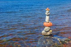 Rock zen pyramid of colorful pebbles standing in the water on the background of the sea. Concept of balance, harmony and. Meditation royalty free stock photos