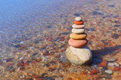 Rock zen pyramid of colorful pebbles standing in the water on the background of the sea. Concept of balance, harmony and. Meditation stock photography