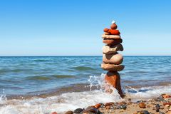 Rock zen pyramid of colorful pebbles standing in the water on the background of the sea. Concept of balance, harmony and. Meditation stock images
