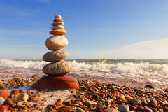 Rock zen pyramid of multi-colored pebbles in the pink rays of the setting sun against the sea. Concept of balance, harmony and. Meditation royalty free stock photography
